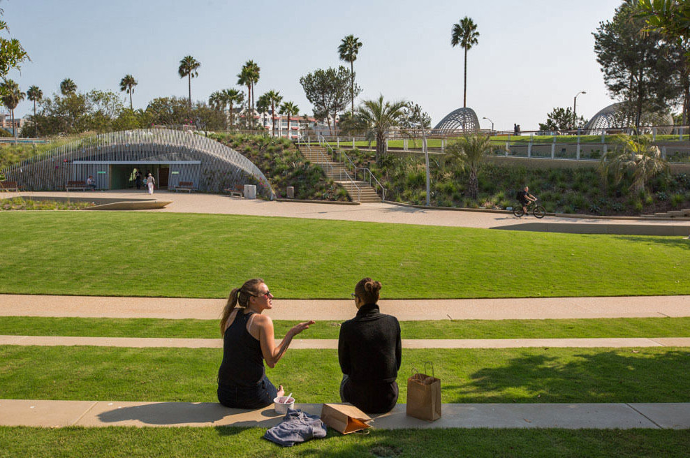 Two people sit on the ground overlooking a park with a large lawn and trees in the distance.