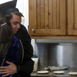 Anita Hallman hugs her son Joseph Hallman following his mock commencement ceremony in their Sugar House home amid the COVID-19 pandemic on Thursday, April 30, 2020. The University of Utah grad earned bachelor's degrees in Latin American studies, Spanish and international business with an emphasis in trade commerce in 2019 with hopes of walking during the spring 2020 commencement ceremony.