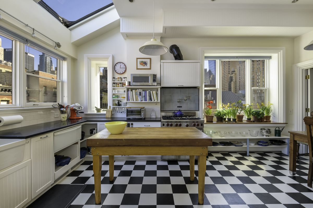 An image of the kitchen looking towards the stove. There's an old butcher block standing island in the middle of the room.