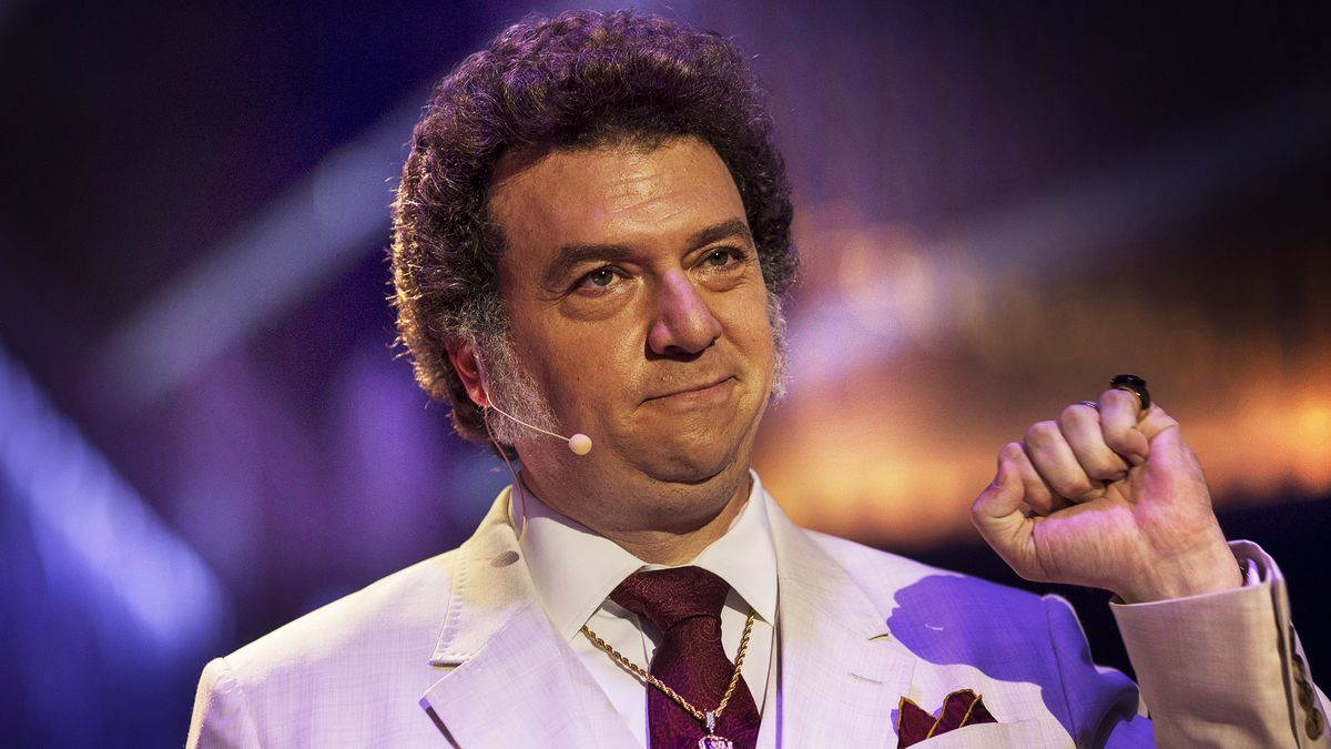 Jesse Gemstone (Danny McBride), wearing a white suit and sporting thick mutton chops, holds up his fist in The Righteous Gemstones
