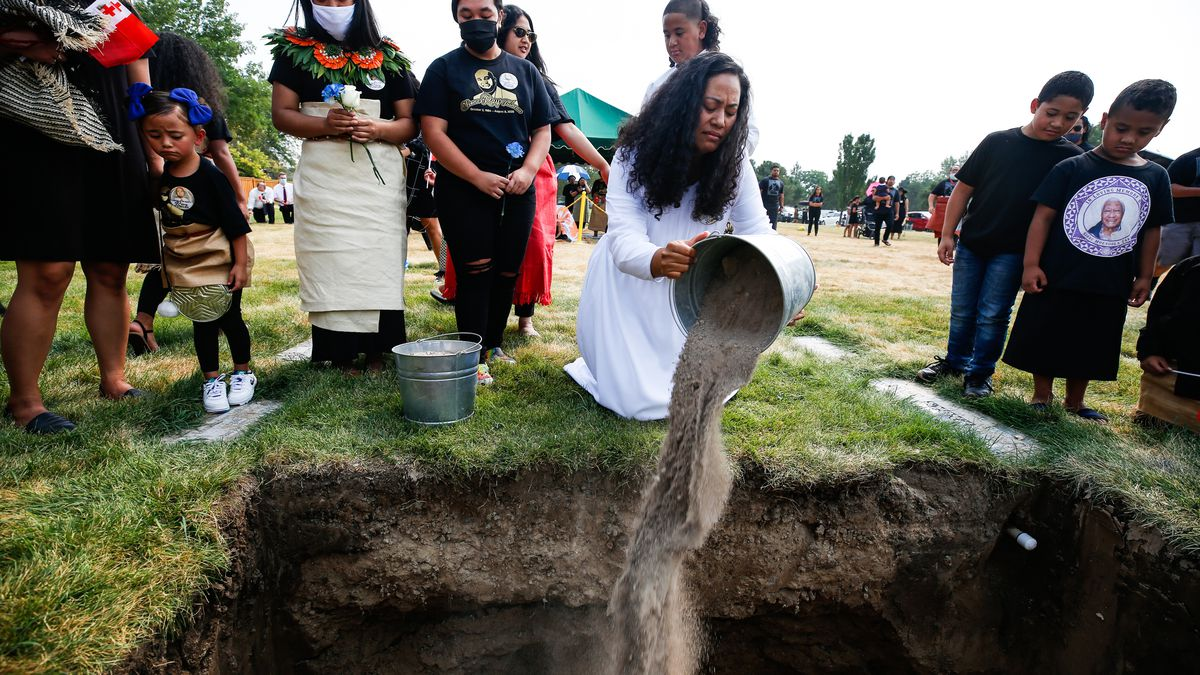 Juliet Tuineau, Ray Tuineau's widow, pours a bucket of soil on her husband's coffin during a burial service at Valley View Memorial Park in West Valley City on Saturday, Aug. 22, 2020. Ray Tuineau was one of the more than 380 Utahns who died because of COVID-19.