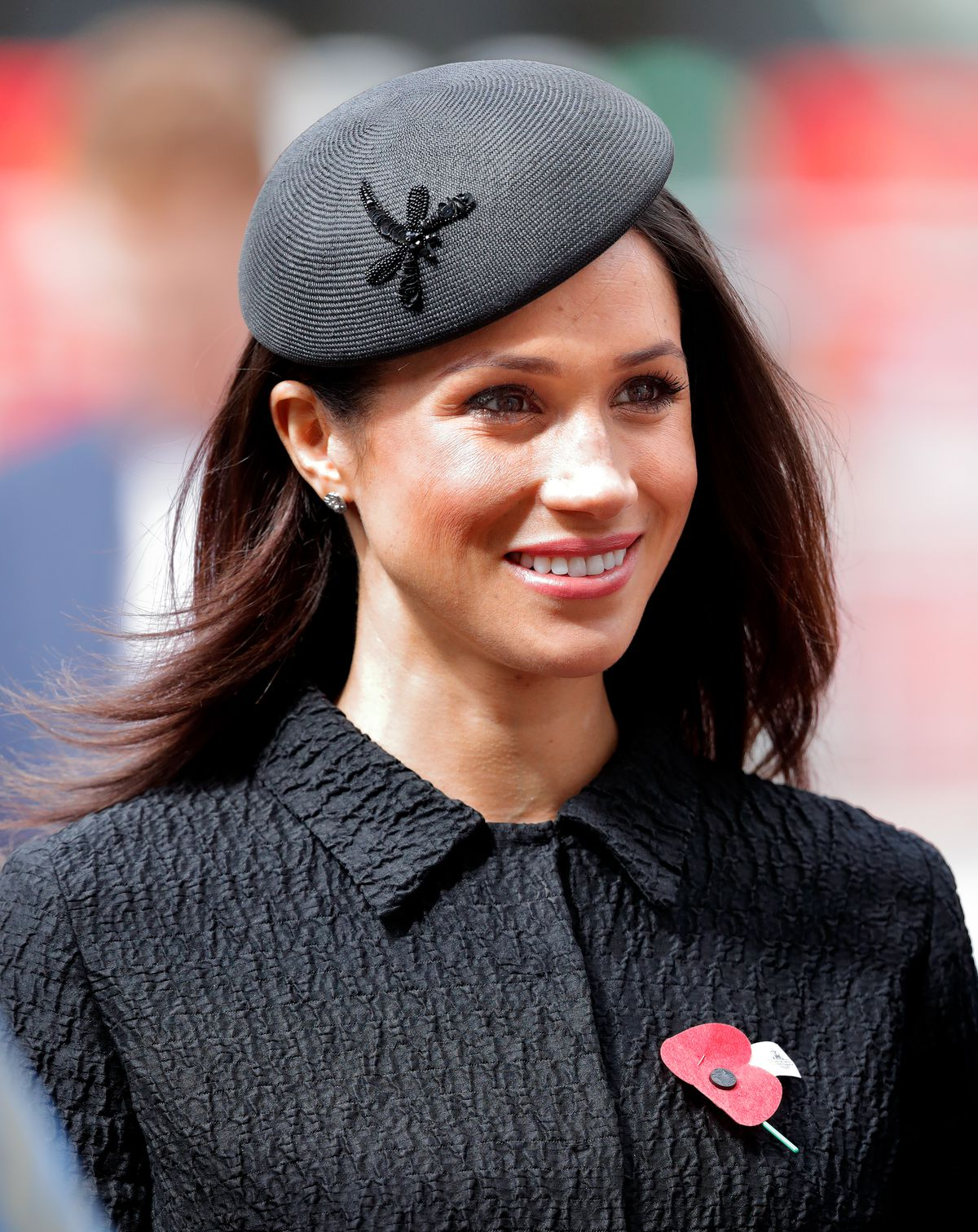 Meghan Markle wearing a black beanie and smiling in the sunshine