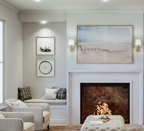 A new living room with a fire going in the fireplace and a built-in bench to the side of that as well as two chairs facing outward.
