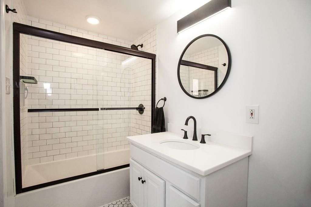 A small bathroom with a glass-enclosed tub.