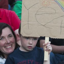 Luke Reymann, 5, holds a sign as he sits with his mother, Kate Reymann, during a same sex marriage celebration at Library Square in Salt Lake City, Monday, Oct. 6, 2014.