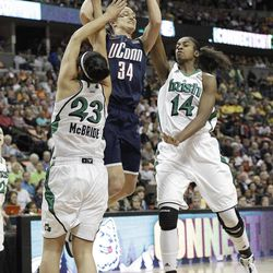Connecticut guard Kelly Faris (34) shoots over the defense of  Notre Dame guard Kayla McBride (23) and Notre Dame forward Devereaux Peters (14)during the first half of the NCAA women's Final Four semifinal college basketball game in Denver, Sunday, April 1, 2012.