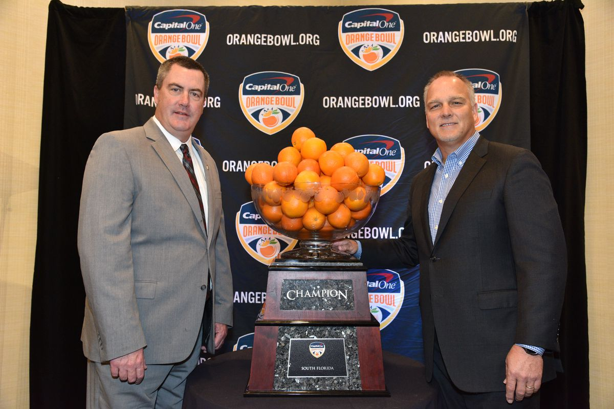 Paul Chryst and Mark Richt by the Orange Bowl trophy.