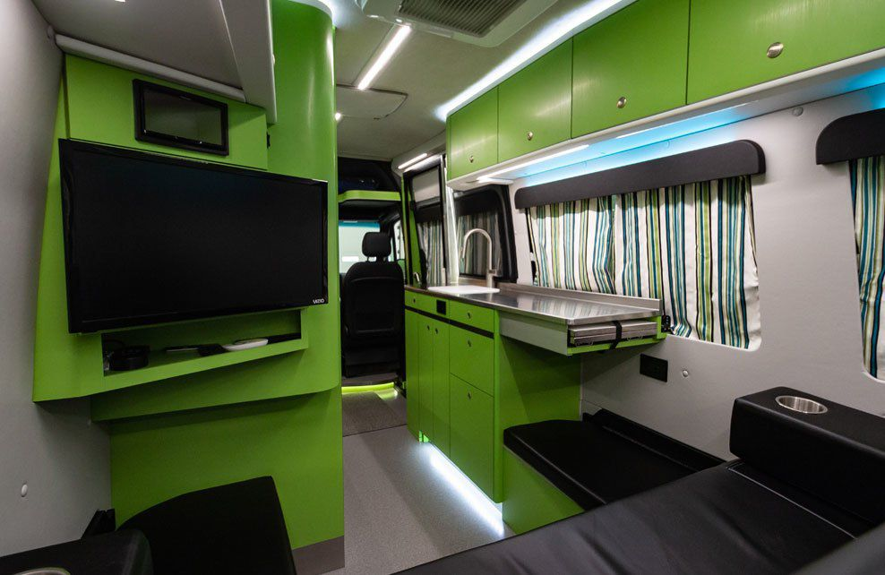 The inside of the camper van has green cabinets and walls, a large TV, and a small galley kitchen with stainless steel counters.
