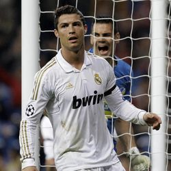Real Madrid's Cristiano Ronaldo from Portugal, foreground reacts in front of Apoel's Urko Pardo of Spain after Ronaldo scored  against Apoel during a second  leg, quarterfinal Champions League soccer match at the Santiago Bernabeu stadium in Madrid Wednesday April 4, 2012. AP Photo/Paul White)