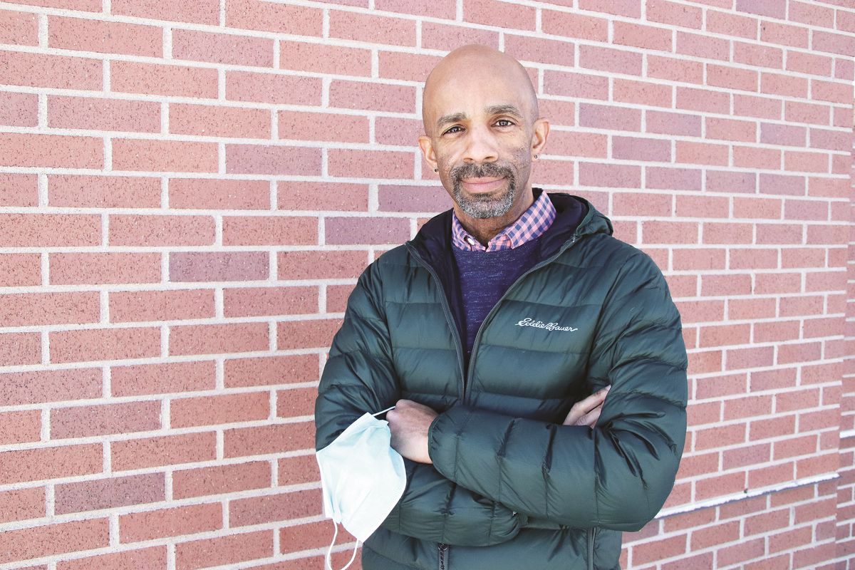 Teacher Rashaan Davis stands against a brick wall. He is wearing a winter coat and holding a mask in his hands.