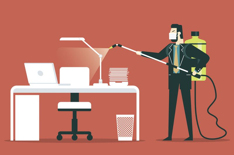 An illustration of a businessman in a suit and tie and face mask spraying cleaning solution from a backpack onto a desk, laptop, and papers.