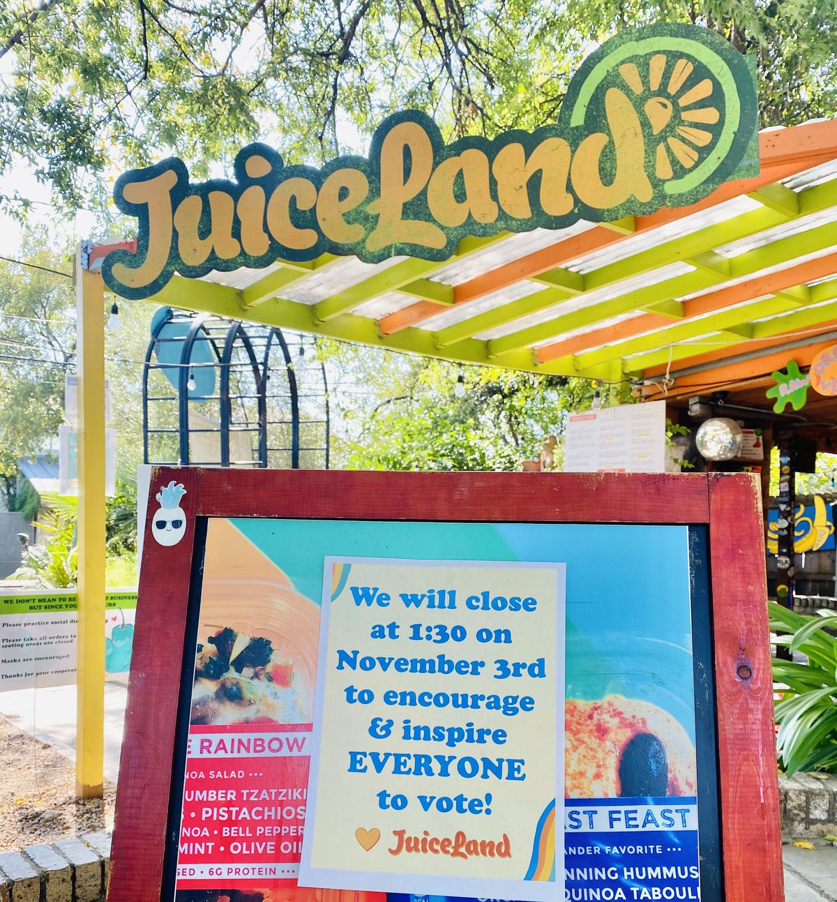 "A tropical-colored pergola and sign reading ""Juiceland"" hangs above a sandwich board announcing that the business will be closed on election day."