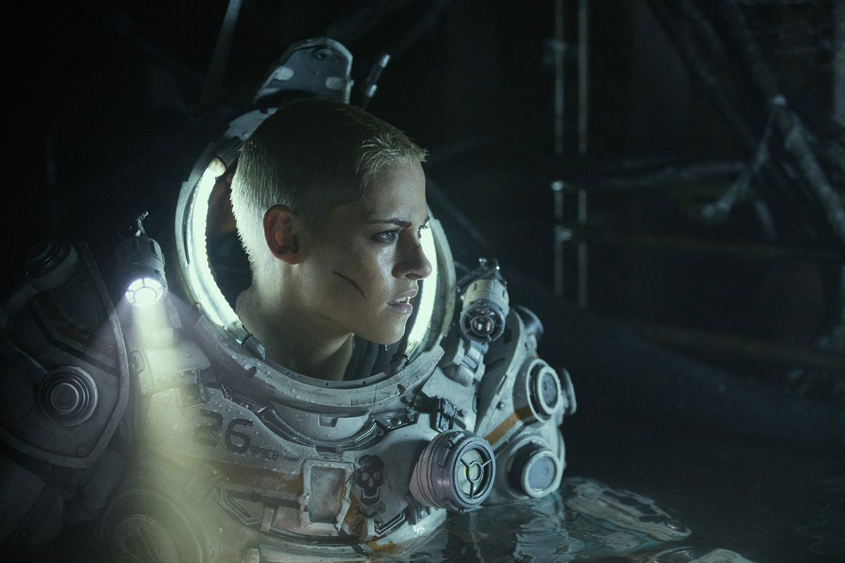 Stewart, with a bloody cut on her cheek, is dressed in a diving suit. The darkness around her is illuminated by her suit's flashlights.