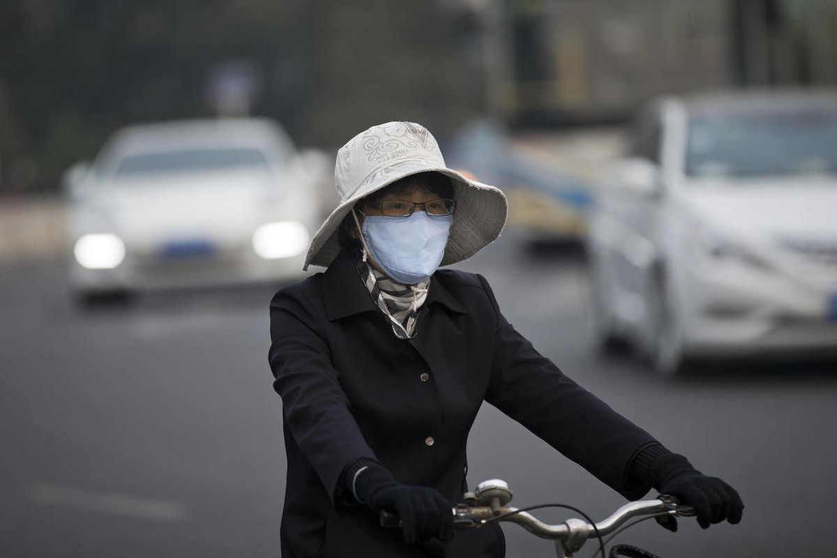 A woman wearing a face mask bicycles on a road in Beijing Tuesday, Oct. 22, 2013.
