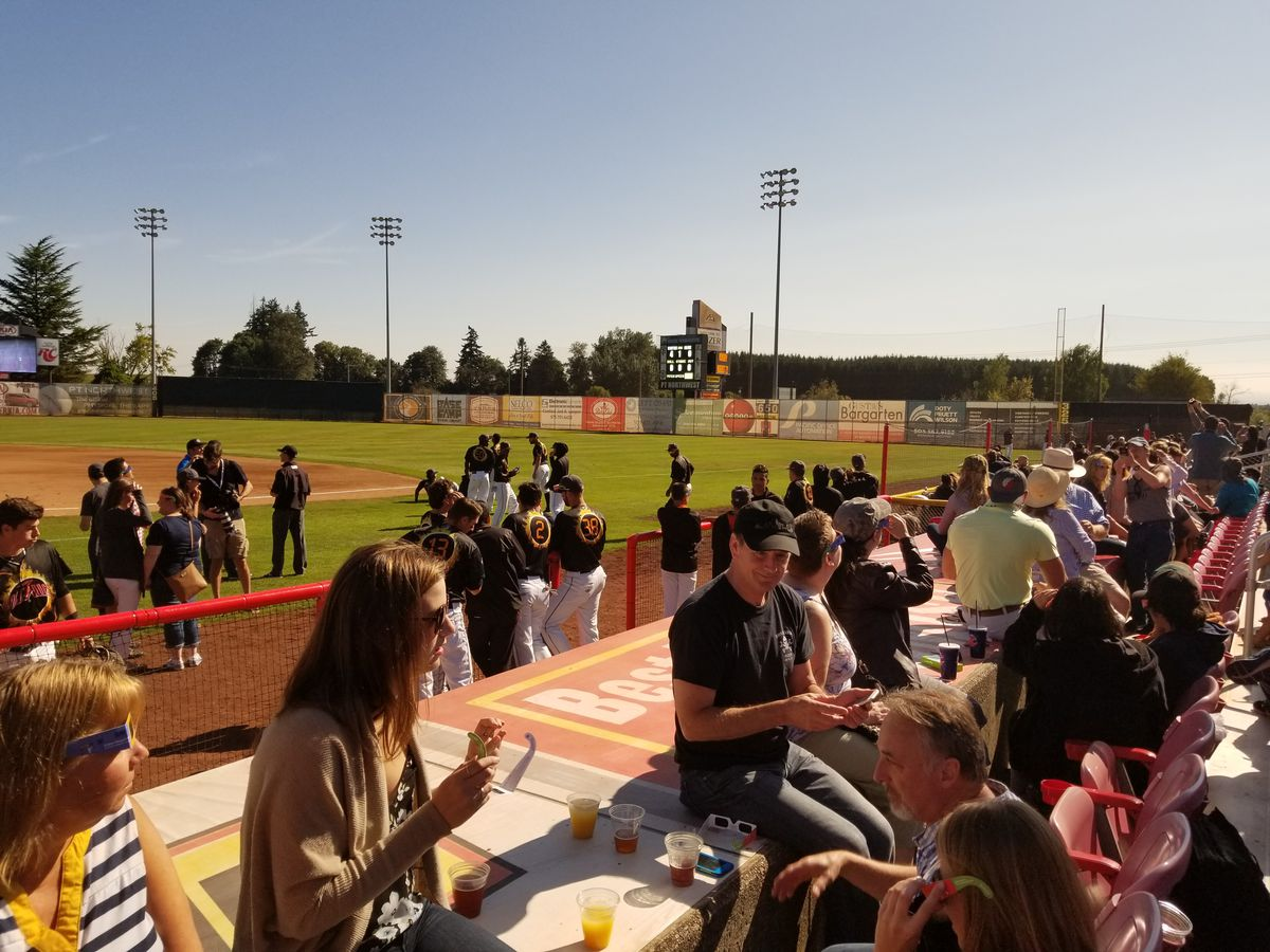 Fans sit on a Volcanoes Stadium dugout waiting for the total solar eclipse