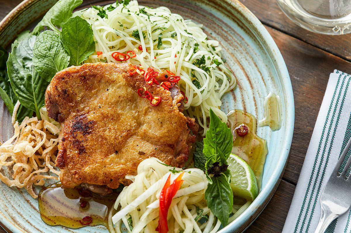 Crispy chicken with vegetables, noodles, herbs, and sauce on a ceramic plate.