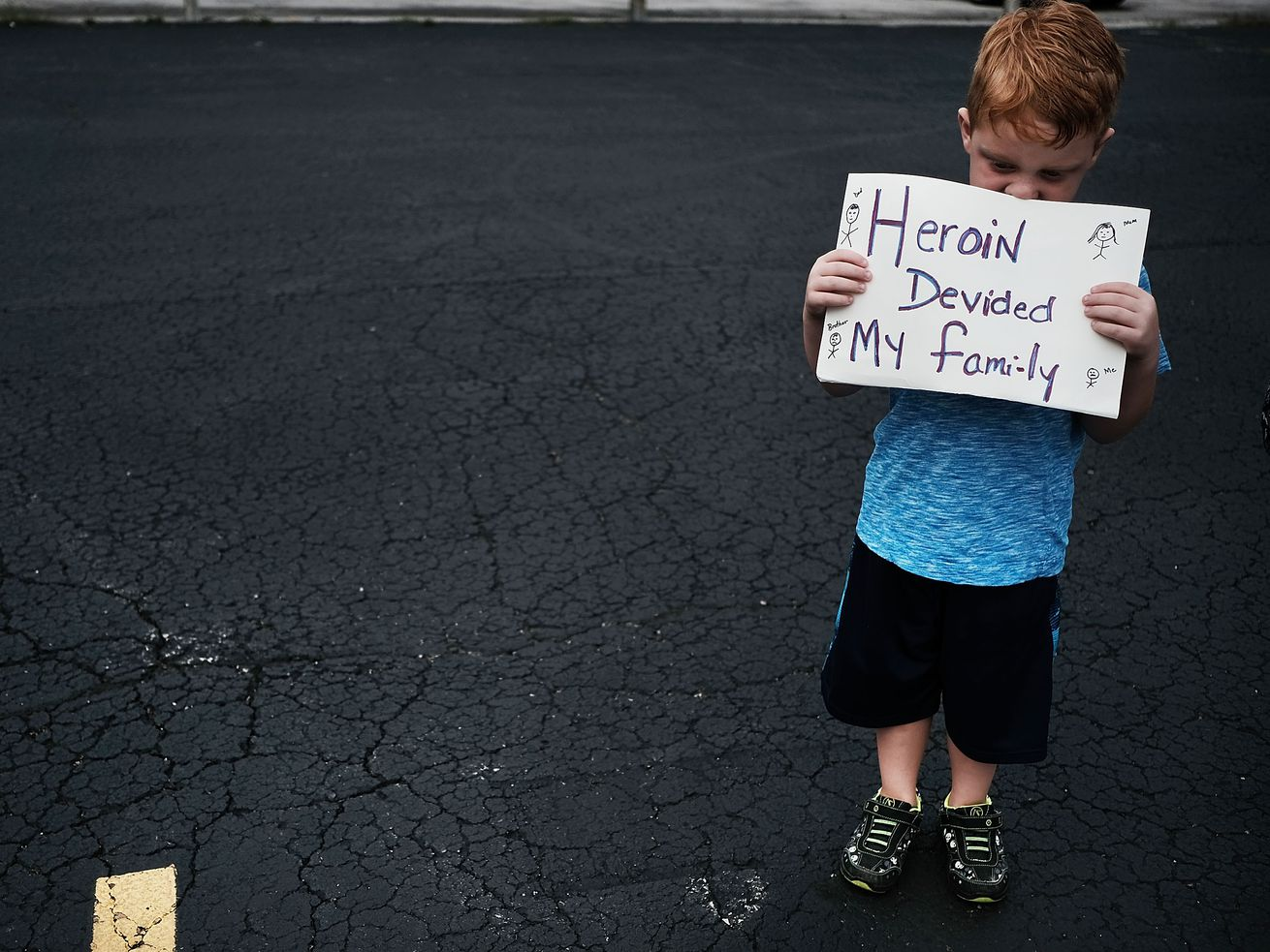 """Derrick Slaughter, 5, attends a march against the opioid epidemic. He holds a sign that reads, """"Heroin divided my family."""""""