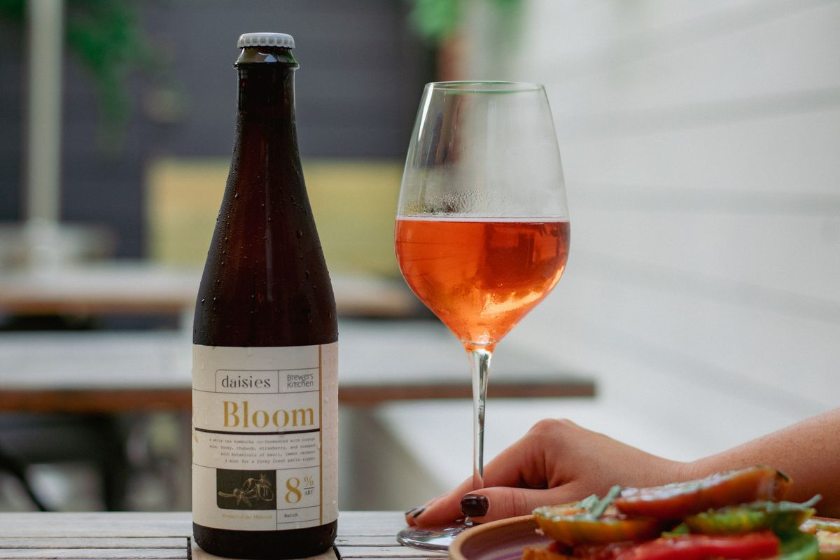 A bottle sits beside a glass of orange-pink kombucha on a wooden table outside