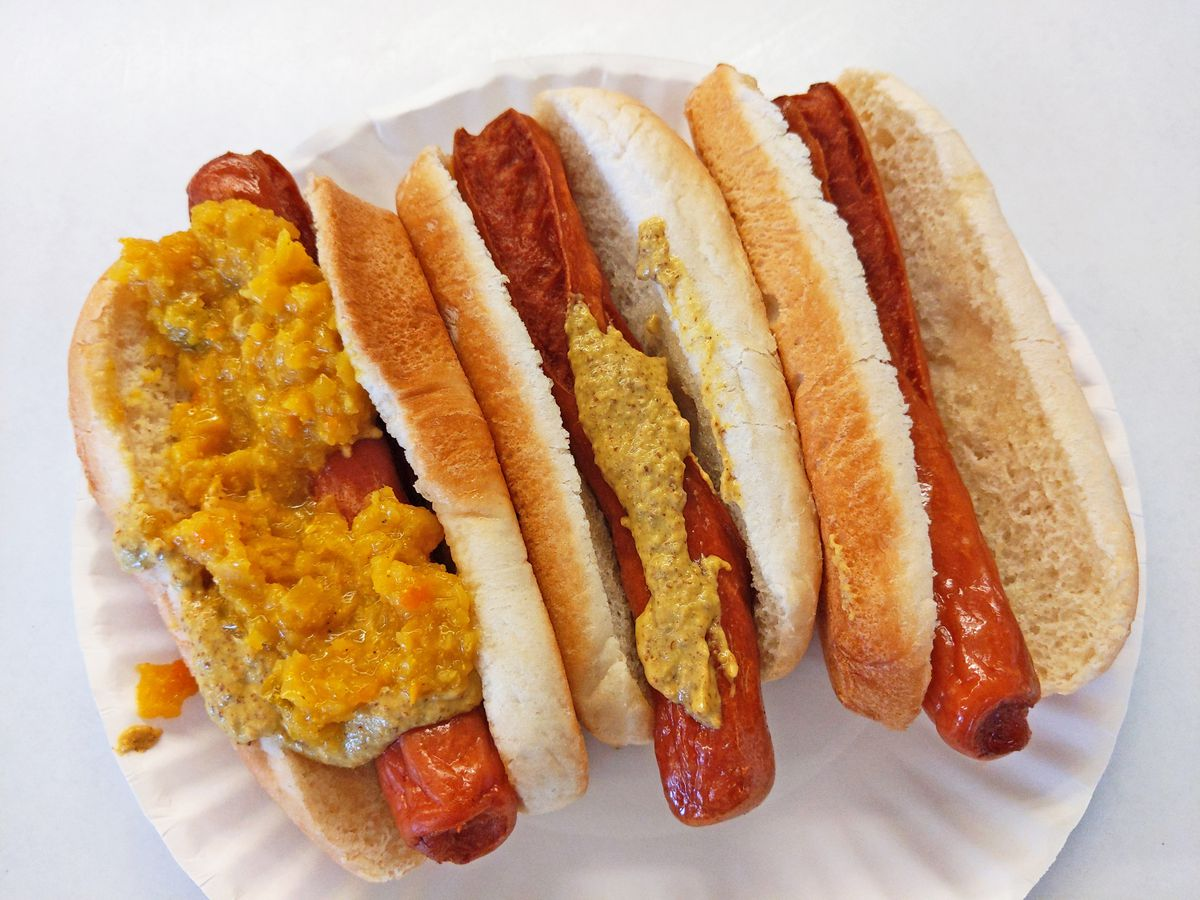 Three hot dogs in buns, with mustardy relish and mustard on two of them.
