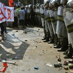 """In this photo taken Sunday, Sept. 16, 2012, Chinese paramilitary police face off with anti-Japan protesters holding up a banner which reads """"Boycott Japanese goods"""" outside the city headquarters of the Communist Party of China in Shenzhen in south China's Guangdong province. (AP Photo) CHINA OUT"""