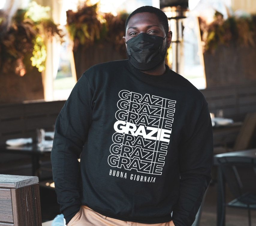 A black man wearing a mask wears a black sweatshirt that says Grazie seven times in white and Buona Giornata at the bottom.