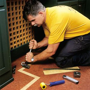 <p>Tom Silva demonstrates how he uses a hard-rubber J-roller to press down the seams of a border stripe, which is inlaid into a sheet of linoleum.</p>
