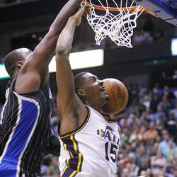 Utah Jazz forward Derrick Favors (15) dunks the ball with Orlando's #11 Glen Davis behind as the Utah Jazz and the Orlando Magic play Saturday, April 21, 2012 in Energy Solutions arena.