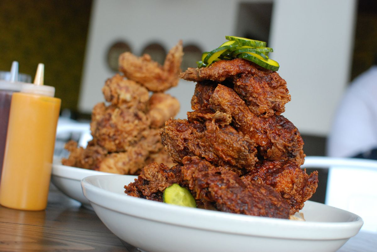 Two plates with towers of Tennessee hot and Southern fried chicken