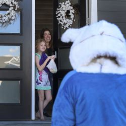 Jennifer Whitehead and her daughter, Julia, smile at the Easter Bunny after receiving Easter eggs at their doorstep in Draper on Friday, April 10, 2020. Due to the COVID-19 pandemic, the Draper City Parks and Recreation Department created the alternative event for children in order to provide holiday festivities while following Centers for Disease Control guidelines. Residents opted-in for the Easter egg delivery service, resulting in 30,000 eggs being delivered on more than 30 delivery routes to 1,045 households.