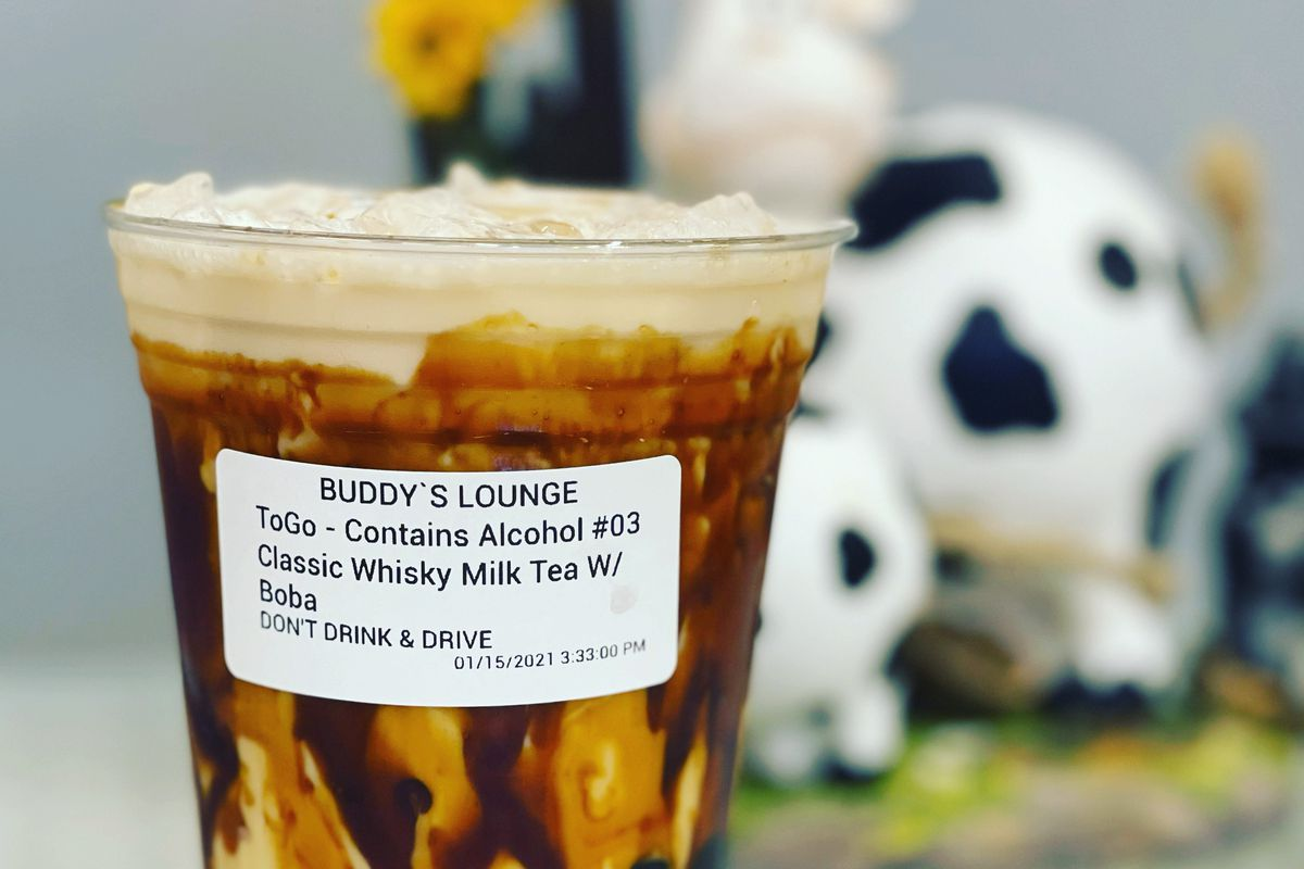 """A cup with tapioca pearls and caramel swirls, with a label that reads """"Buddy's Lounge"""""""