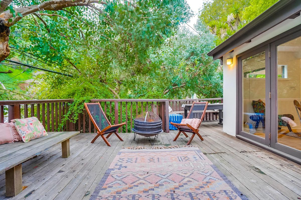 A big outdoor deck with a fire pit and trees hanging over it.