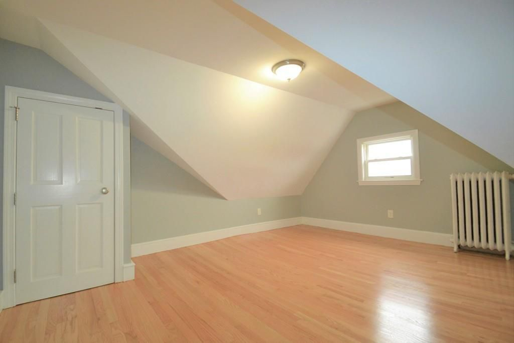 An empty bedroom with sloped ceilings, a closed closet door, a radiator, and a window.