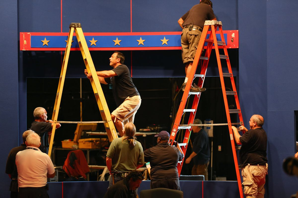 Workers prepare the stage for debate.