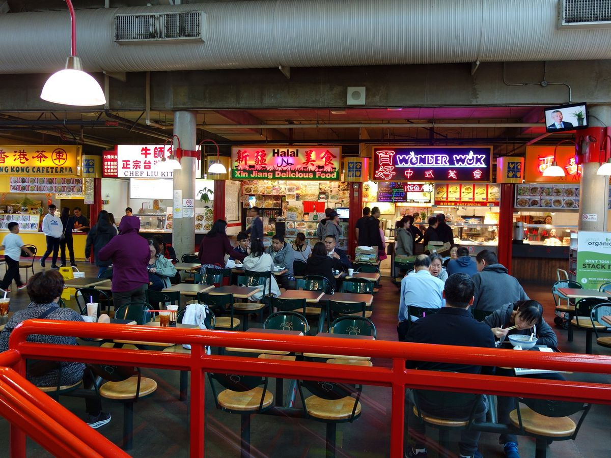 Diners fill food court tables in front of several vendors in a large mall space