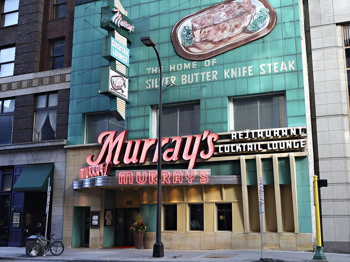 The green outdoor facade with large red neon lights outside Murray's