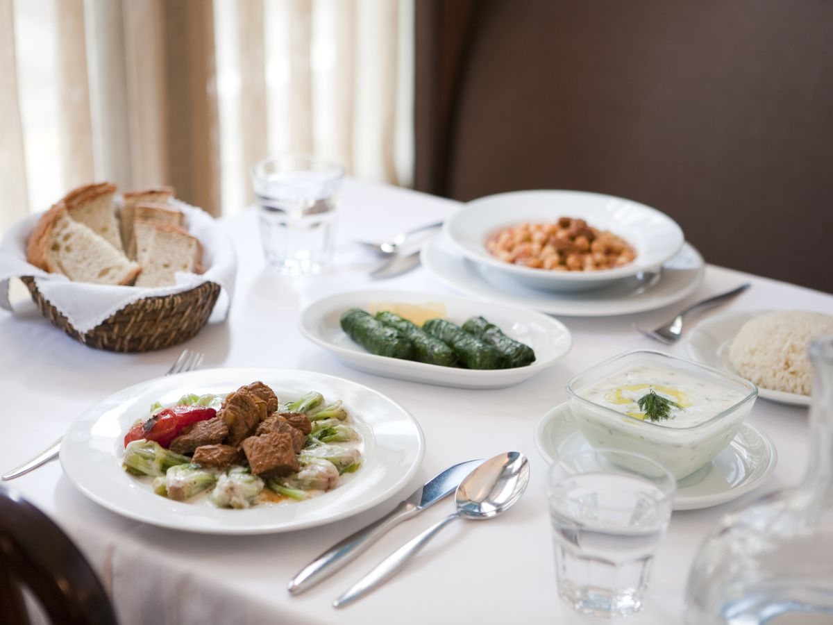 A table set with white tablecloth and dishes including dips, bread, meat, and stuffed grape leaves, against a sunny shaded window