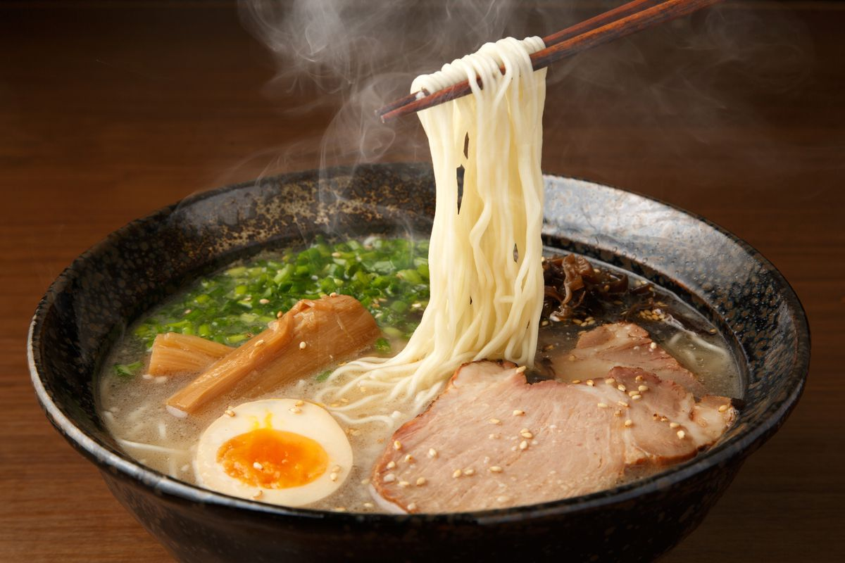 A steaming bowl of pork belly ramen with chopsticks holding up long strands of noodles