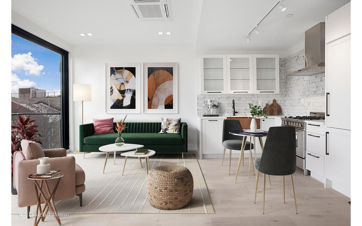 A living area with a large window, a green couch, two small coffee tables, and a kitchen with white cabinetry on the right side.