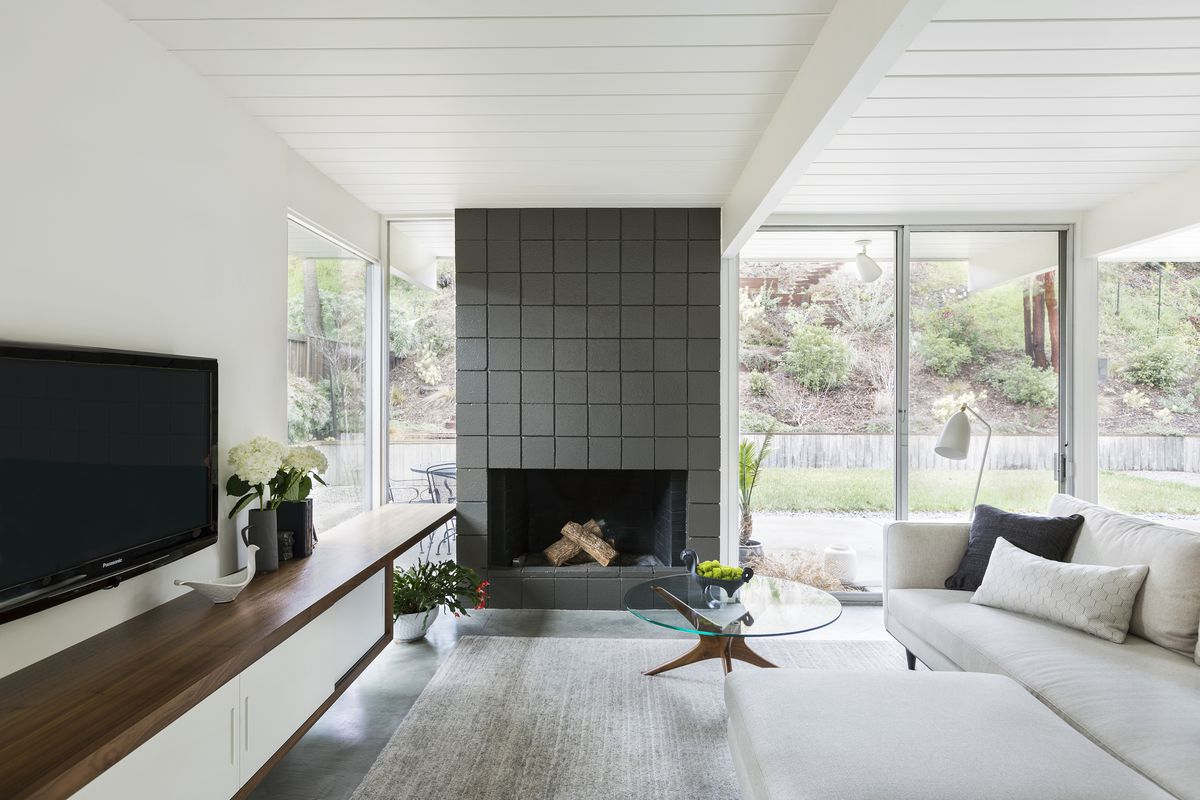 A living room is lined with floor-to-ceiling glass doors and windows, and features a fireplace with a gray surround. A media cabinet's counter extends past a window to make a window seat.