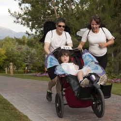 Joe Reardon and Anita Reardon push their daughter, JulieLynn Reardon, during the Fairy Tale 5K at Thanksgiving Point in Lehi Saturday, June 21, 2014. In spite of being diagnosed with a severe form of epilepsy, JulieLynn Reardon is on grade level in most subjects.