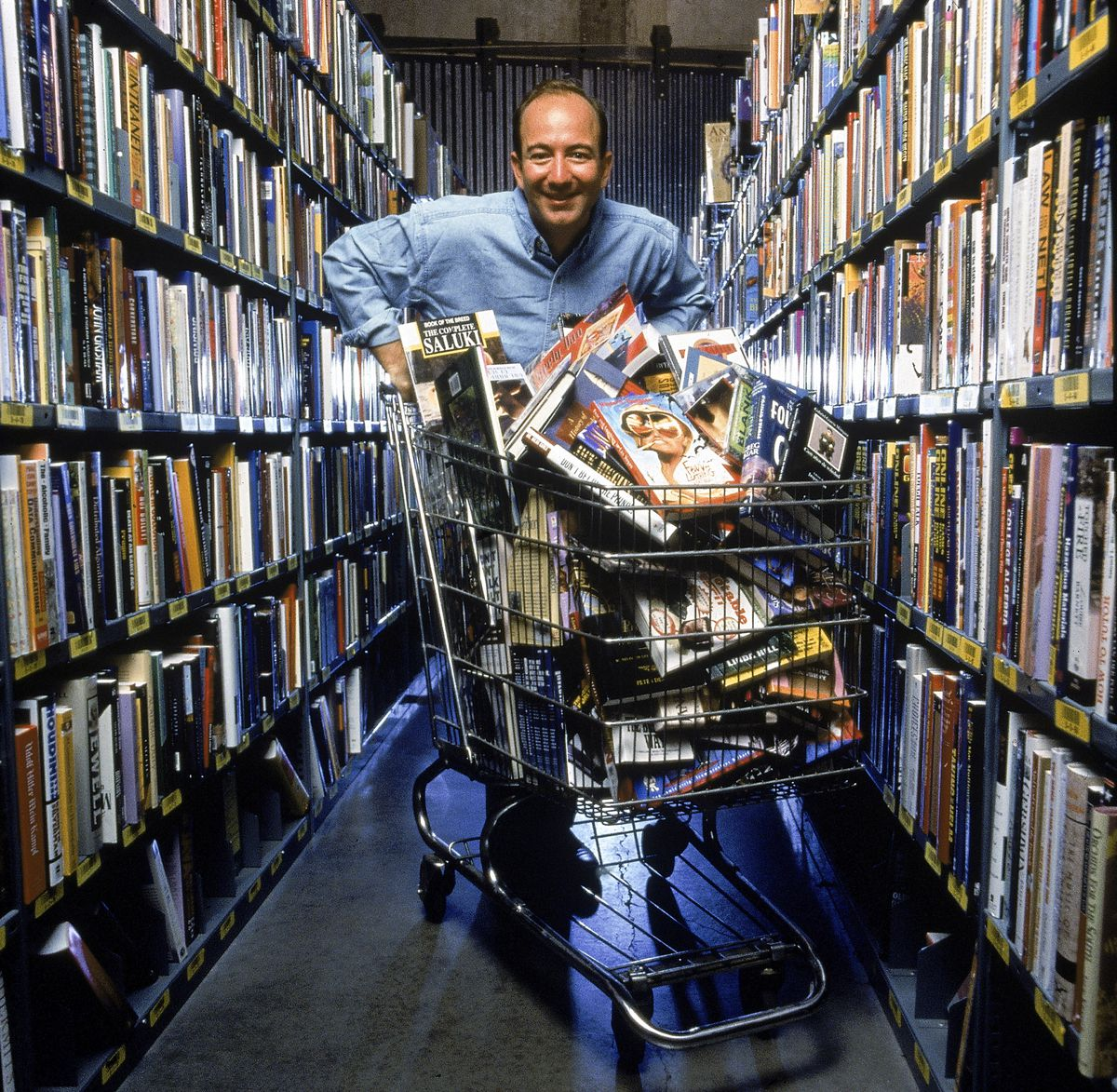 Amazon.com CEO Jeff Bezos pushing a shopping cart full of books back in 1998.