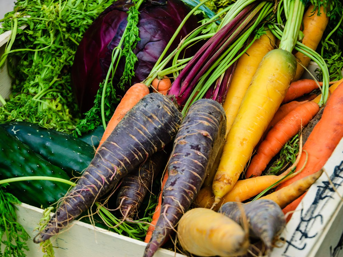 Different color carrots, red cabbage and cucumbers in wooden box. Fresh organic produce from a local farmers market in Paris (France).