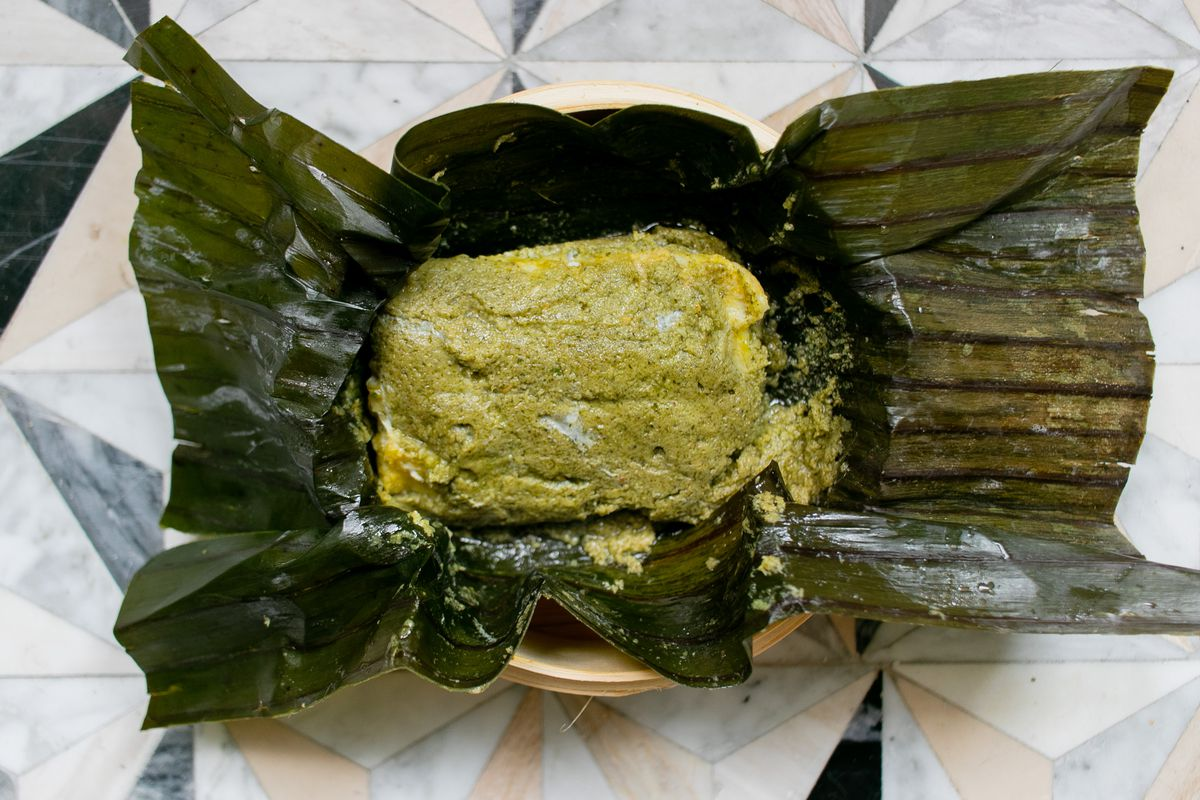 A green square of steamed fish with coconut in the center of unwrapped green banana leaves, set on a light patterned table.
