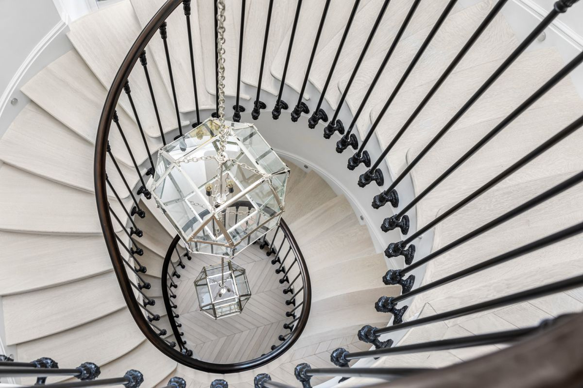 A spiral staircase with black railings.