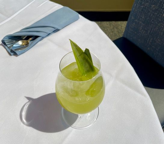 A green cocktail on a white tablecloth at Mr. A's.
