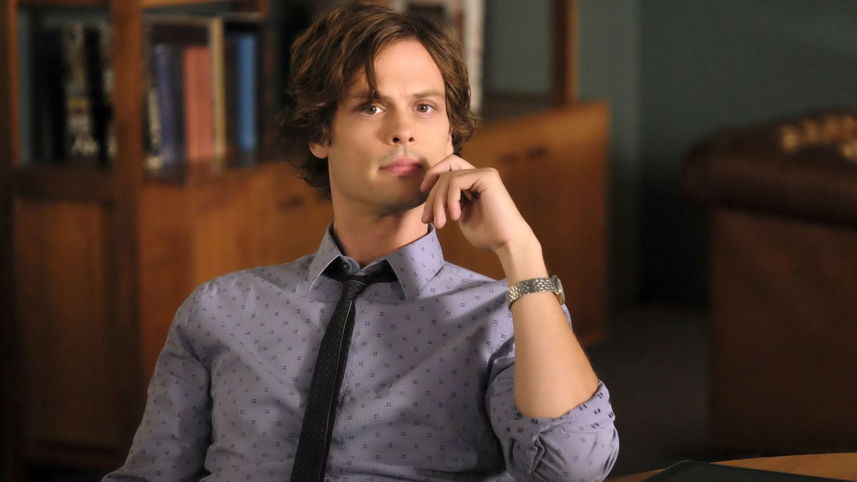 Spencer Reid (Matthew Gray Gubler), a brown-haired, clean-shaven main in a gray dress shirt and skinny black tie, on Criminal Minds
