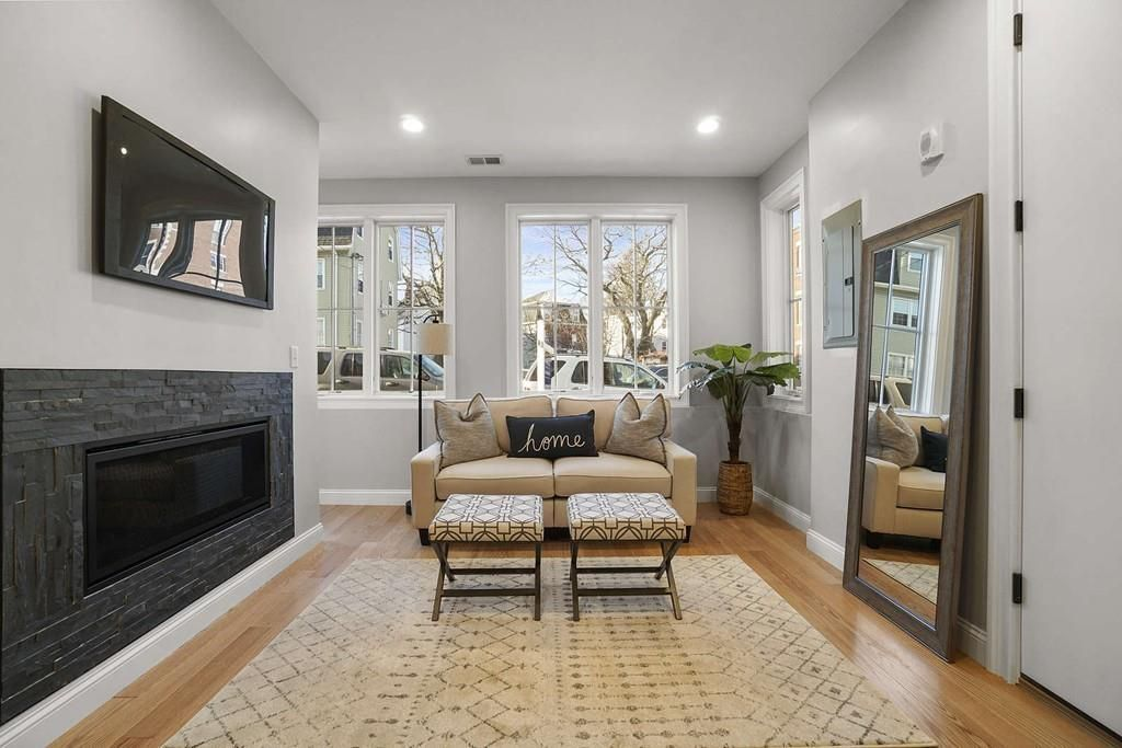 A spacious modern living room with a fireplace and two windows at the end.