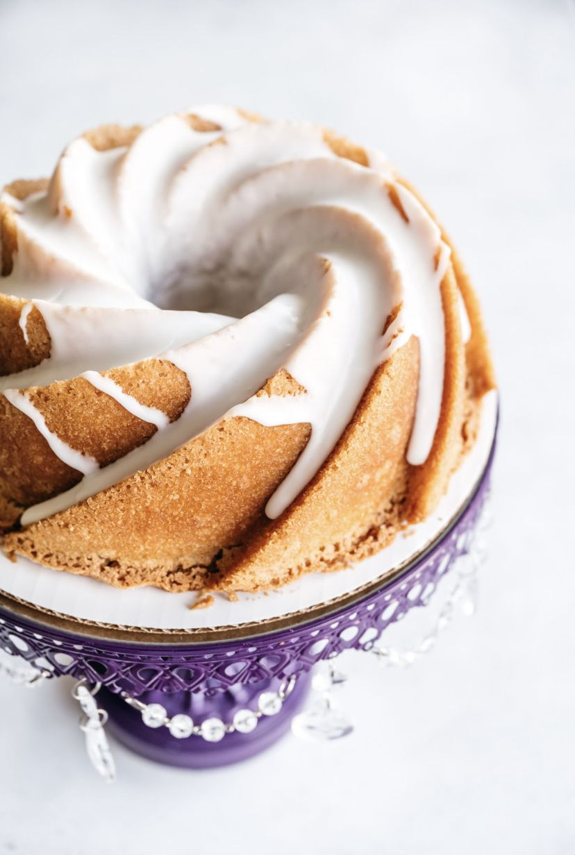 A lemon bundt pound cake on a cake stand is drizzled with vanilla frosting