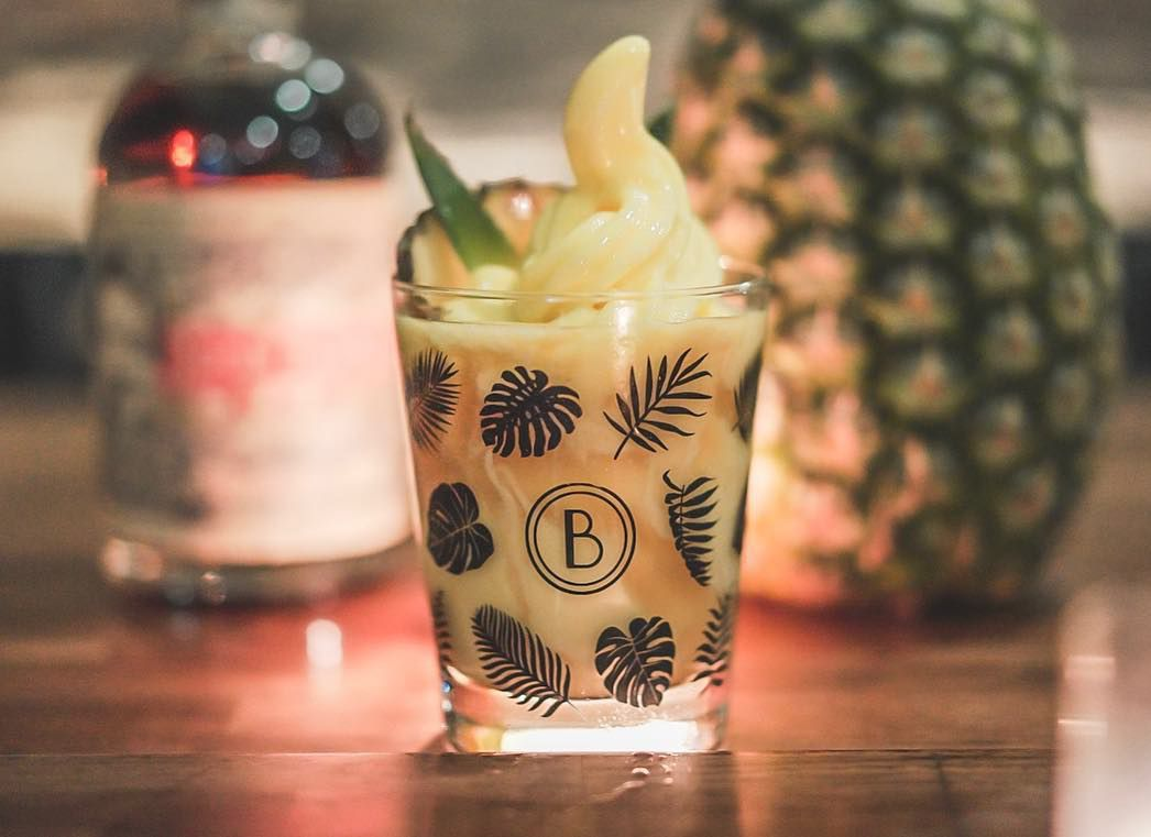 A boozy dole whip sits in a Blossom Bar branded glass, with a pineapple in the background