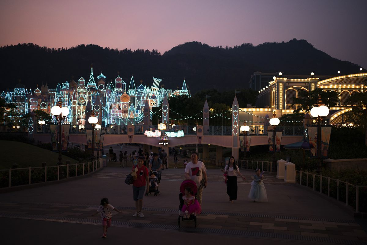 In this Oct. 11, 2019 photo, visitors walk at dusk in Hong Kong Disneyland in Hong Kong. The body-blow of months of political protests on Hong Kong's tourism is verging on catastrophic for one of the world's great destinations.